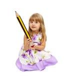 拿着大铅笔的小女孩 免版税图库摄影