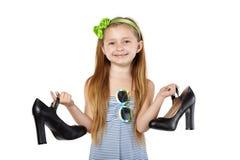 拿着大黑色母亲鞋子的微笑的女孩 免版税库存照片