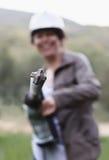 拿着大直径的冲击式钻机的微笑的妇女 Selectiv 免版税图库摄影