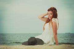 拿着太阳帽子的红头发人妇女说谎在海滩 库存图片