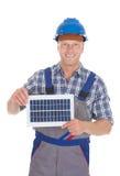 拿着太阳电池板的确信的安装工 库存图片