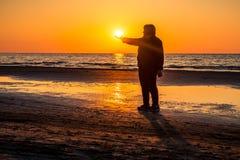 拿着太阳的中年妇女在海边 库存图片