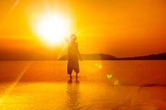 拿着太阳的人剪影在明亮的金黄热带日落 免版税库存照片