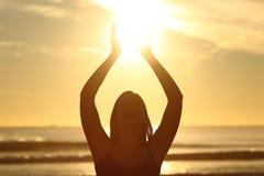 拿着太阳的妇女在日落 库存照片