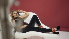 拿着太阳镜和在扶手椅子的白肤金发的模型被拍摄 股票视频