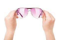 拿着太阳镜的女性手 免版税库存照片
