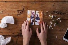 拿着夫妇的被撕毁的图片在爱的无法认出的哀伤的妇女 免版税图库摄影