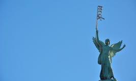 拿着奇怪的霓虹灯的一个女性天使的雕象 免版税库存照片