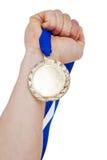 拿着奥运金牌奖牌的手特写镜头 免版税库存图片