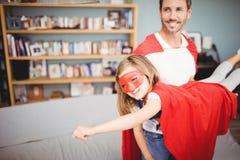 拿着女儿佩带的超级英雄服装的微笑的父亲 库存图片