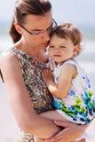 拿着女儿的哀伤的母亲 免版税库存照片