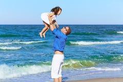 拿着女儿的家庭父亲演奏海滩 免版税图库摄影