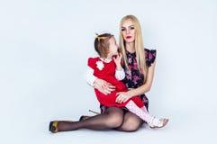 拿着女儿的年轻美丽的母亲 免版税图库摄影