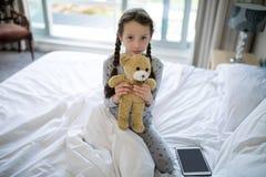 拿着女用连杉衬裤的女孩在卧室涉及床 库存图片