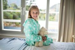 拿着女用连杉衬裤的微笑的女孩在卧室涉及床 库存图片