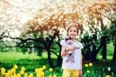 拿着女用连杉衬裤的逗人喜爱的愉快的儿童女孩涉及与黄色郁金香的春天步行在背景 免版税库存照片