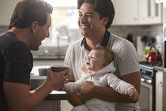 拿着女婴的男性快乐夫妇在他们的厨房里 免版税库存照片