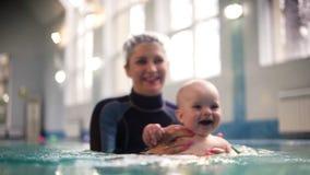 拿着她儿子婴孩和她的泳装的母亲获得乐趣在游泳场 一种健康生活方式的概念为 股票视频