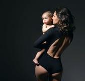 拿着她可爱的婴儿儿童女婴的年轻母亲妇女 库存图片
