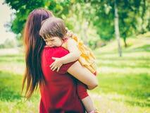 拿着她哭泣的逗人喜爱的女婴的母亲 免版税库存图片
