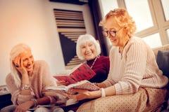 拿着她喜爱的书的宜人的好妇女 免版税库存图片