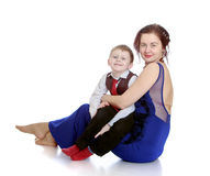 拿着她心爱的儿子的时髦的年轻母亲 库存图片