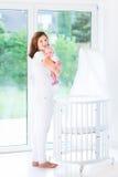 拿着她新出生的婴孩下个小儿床的年轻母亲 库存图片