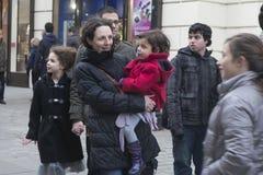 拿着她的一件红色外套的一件黑夹克的一名妇女女婴 他们看演员的表现,科文特花园 库存照片