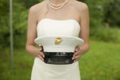 拿着她的丈夫的军队帽子的新娘 免版税库存照片