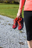 拿着她的体育鞋子的运动员妇女 库存照片
