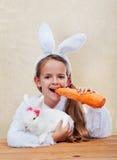 拿着她的兔宝宝的愉快的复活节服装女孩 免版税库存图片