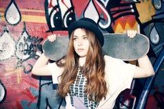 拿着她的冰鞋的年轻溜冰者女孩在都市地方 免版税库存图片