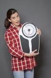 拿着她的减重成功的满意的30s妇女重量标度 免版税库存照片