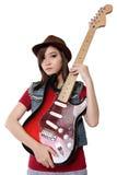 拿着她的吉他,在白色背景的华美的亚裔女孩 免版税库存照片