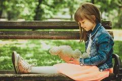 拿着她的喜爱被充塞的玩具的女孩 图库摄影