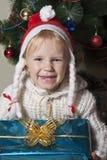 拿着她的圣诞节礼物的小女孩 图库摄影
