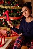 拿着她的在圣诞树前面的愉快的女孩礼物 库存照片