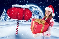拿着她的大礼物盒的圣诞老人帽子的愉快的妇女反对数位引起的圣诞节背景 免版税库存图片