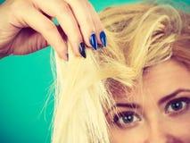 拿着她的头发末端的白肤金发的妇女 图库摄影