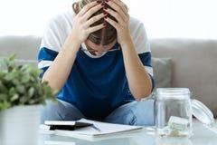 拿着她的头用手的沮丧的年轻女人,当在家时计数储款 图库摄影