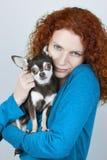 拿着她的奇瓦瓦狗狗的美丽的红色头发妇女画象被隔绝在灰色背景 免版税库存图片