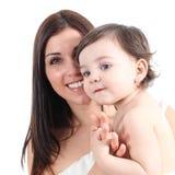 拿着她的女儿的一个美丽的母亲的画象 免版税库存图片