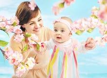 拿着她的女儿的微笑的妈妈 免版税库存图片