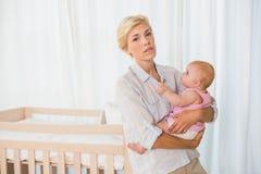 拿着她的女婴的Beauitiful妇女 免版税图库摄影