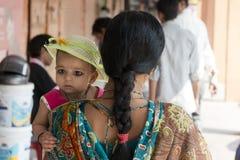 拿着她的她的胳膊的印地安妈妈女儿 库存照片