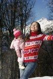 拿着她的她的胳膊的愉快的母亲女儿在a 免版税库存图片