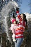 拿着她的她的胳膊的愉快的母亲女儿  免版税图库摄影