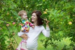 拿着她的小女儿的可爱的年轻孕妇 库存照片