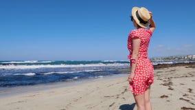 拿着她的帽子的年轻可爱的妇女,当红色礼服在强风时拍动 她在看起来空的海滩站立towar 股票录像