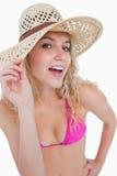 拿着她的帽子边缘的可爱的白肤金发的少年 免版税库存图片